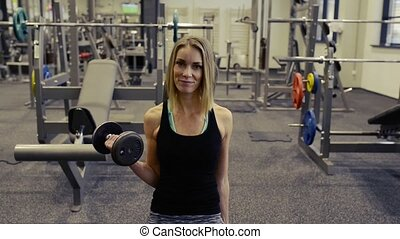 Beautiful blond woman in gym working out with weights -...