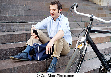 Man is resting next to his bike and using phone