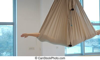 In a closed hammock for yoga in the air, a woman lies and...