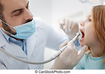Professional child dentist doing a regular procedure - Sit...