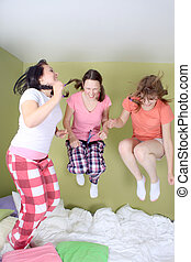 Girls jumping on bed - Teen girls having a sleepover jumping...