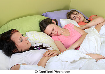 Slumber party - Three pretty teenage girls sleeping on a bed...