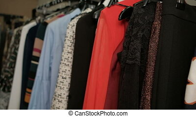 Closeup shooting rack with hangers with different colorful clothes