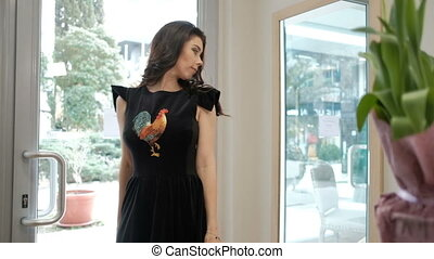 woman demonstrates new dress, turning in front of mirror in store