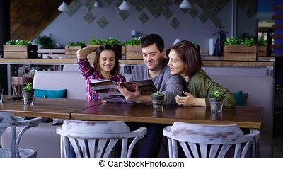 Three attractive young people in a cafe or restaurant choose...