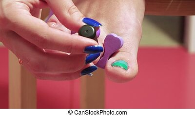 Pedicure of small nails on the feet - Girl doing a pedicure...