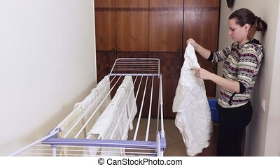 Girl is hanging laundry on dryer - On tumble-dryer brunette...