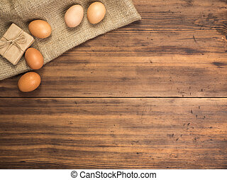 Brown chicken eggs and gift box lay on a piece of burlap on...