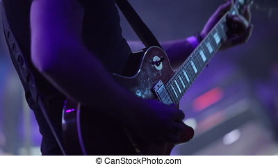 Guitar player on stage at a concert rocking the audience