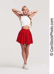 Girl with perfect body in red skirt on a white background.