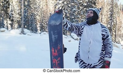 Portrait of a young man snowboarder standing with his...