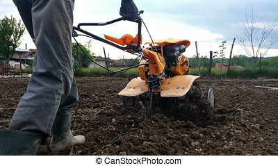 Man plowing field using a cultivator