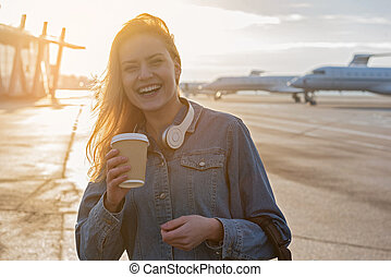 Outgoing female tasting beverage outdoor in airport -...