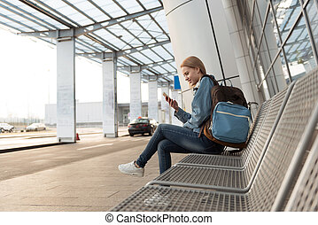 Cheerful female watching at cellphone outdoor - Happy young...