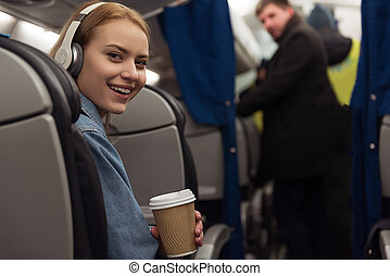 Beaming girl listening music in cabin - Portrait of young...