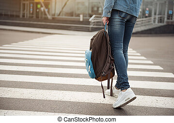 Young tourist stepping across route - Close up of legs of...