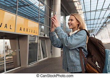 Happy female making pictures by cellphone near airport -...