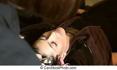 Woman client washing head at the salon. Beauty and hair care...
