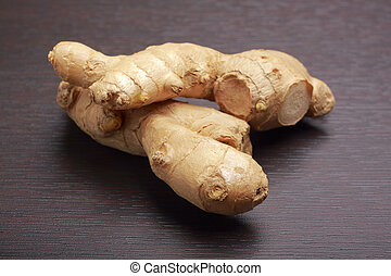 Ginger root rhizome lying on dark board