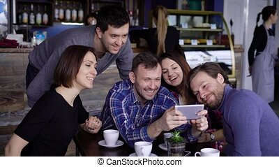 Attractive guys and girls in the cafe, do selfie on the phone. A company of friends is photographed together for social networks. Students of designers have a day off