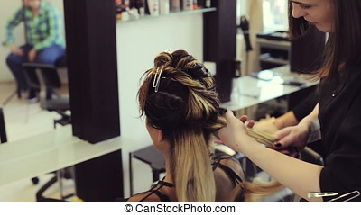 Woman getting her hair done in the salon. Beauty and...