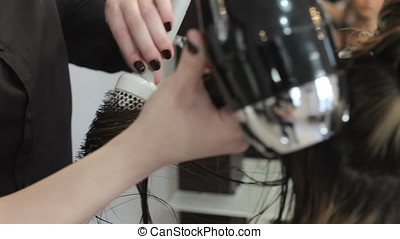 Beautiful woman getting her hair done in the salon