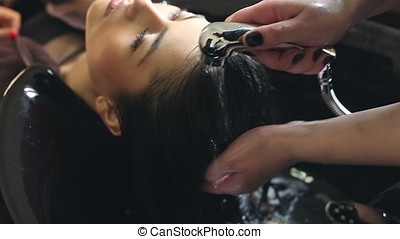 Woman with hairdresser washing hair at the salon - Young...