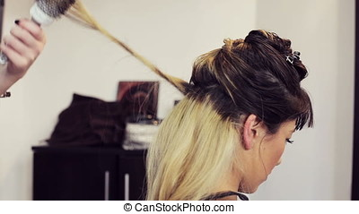 Gorgeous woman getting her hair done in the salon. Beauty...