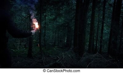 Man With Flare Descends Forest Slope - Man walks down...