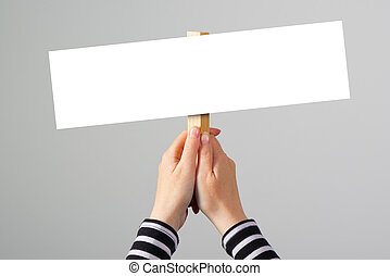 Female hand holding blank mockup banner sign as copy space -...