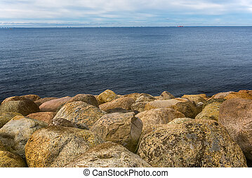 Large rocks on sea shore water's edge, seascape on cold...