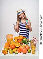 Girl in swimsuit and summer hat with a lot of citrus fruits...