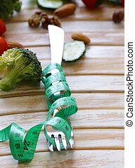 Diet concept - fork with measuring tape on a wooden table