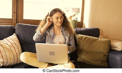 Beautiful teenage girl at home sitting on couch, laptop on her lap, wearing headphones, listening music.