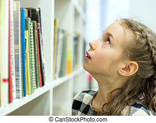 Pretty little girl looking for a book in library.