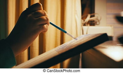 Woman Artist Sitting at a Table Draws a Picture at Home