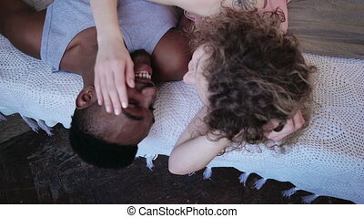 Fight by pillows of loving multiracial couple in pajamas. Man and woman having fun in the morning in bedroom together.