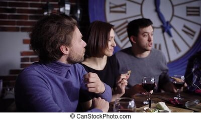 A group of attractive young people in a modern restaurant at a table with snacks and wine. Men and girls drink red wine and eat snacks. Friends celebrate a successful contract or birthday.