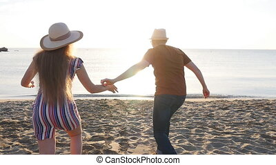 Two people running playful holding hands on summer travel...