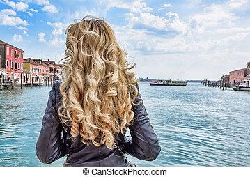 Woman walking in Murano island Italy. Traveler or tourist...