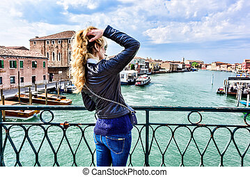 Woman walking in Murano island Italy. Traveler or tourist...