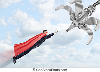 A businessman wearing a red superhero cape flying through...
