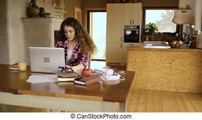 Upset teenage girl at home, working on notebook, studying -...