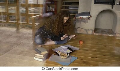 Teenage girl with tablet sitting on the floor, studying -...