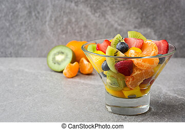 Fruit salad in crystal bowl on gray stone