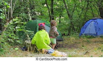 Two children play in the clearing near the tents in the...