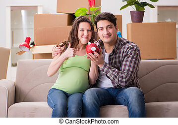 The young couple saving money for baby to be born - Young...