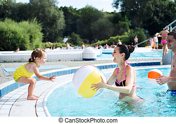 Mother, father and daughter in swimming pool. Sunny summer....