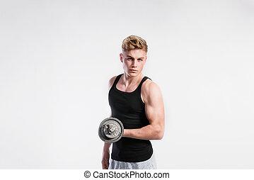 Handsome fitness man holding dumbbell, studio shot. -...