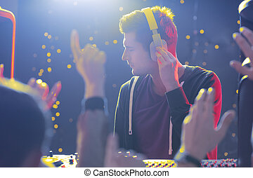 Disc jockey and crowd - Disc jockey wearing headphones and...